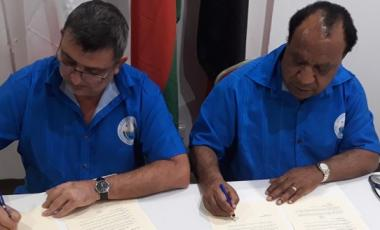 Philippe Germain et Rimbik Pato signent l'accord de coopération.